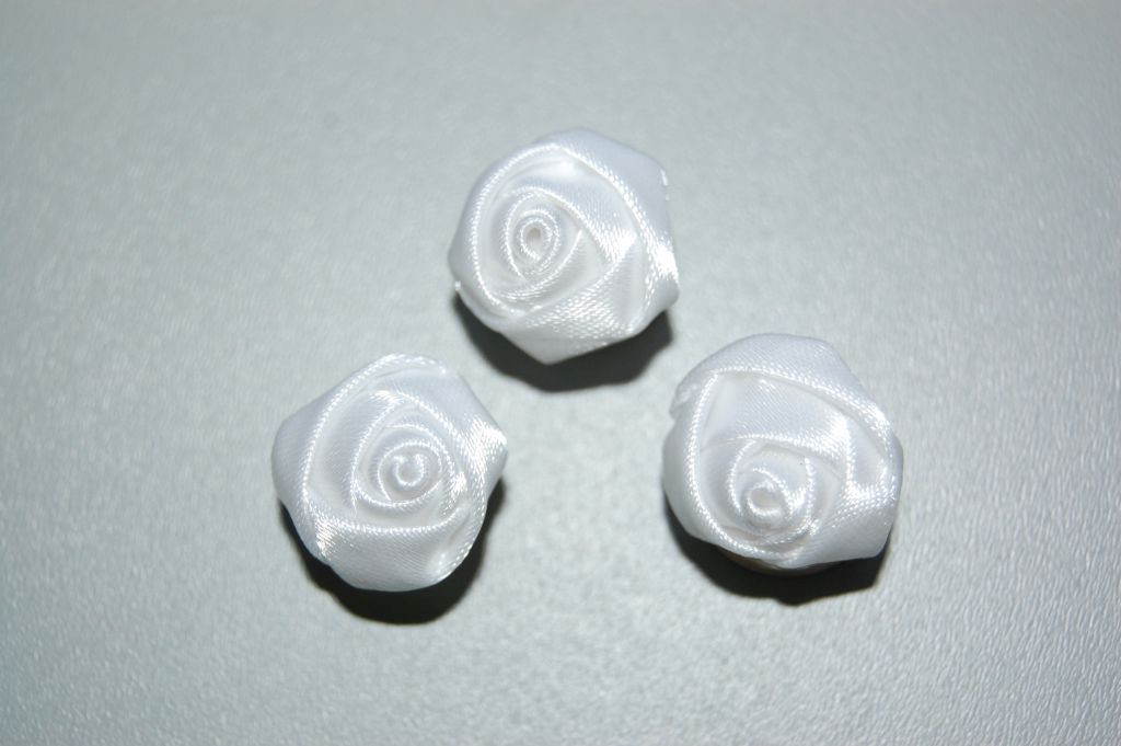 Three white fabric roses